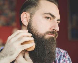 Uomo con barba lunga e folta usa una spazzola