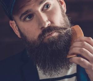 Uomo con barba lunga e folta usa un pettine