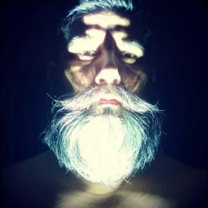 Uomo con la barba si fa un selfie con il flash