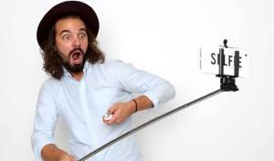 Uomo con barba e cappello usa il selfie stick