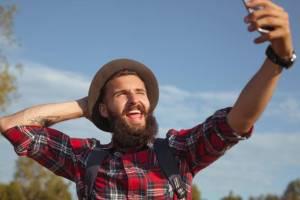 Uomo con barba e cappello si fa un selfie