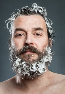 Uomo che sta lavando la barba con il sapone