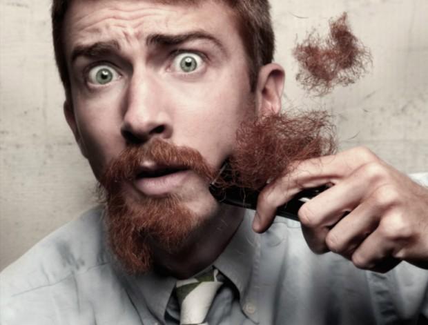 Uomo che si rade la barba con un rasoio elettrico