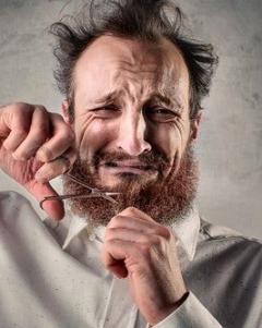 Uomo triste taglia barba con le forbici