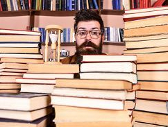 Un uomo con la barba dietro pile di libri