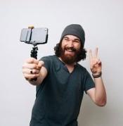 Uomo con barba che si fa un selfie