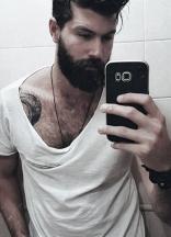 Ragazzo tatuato con la barba si fa un selfie