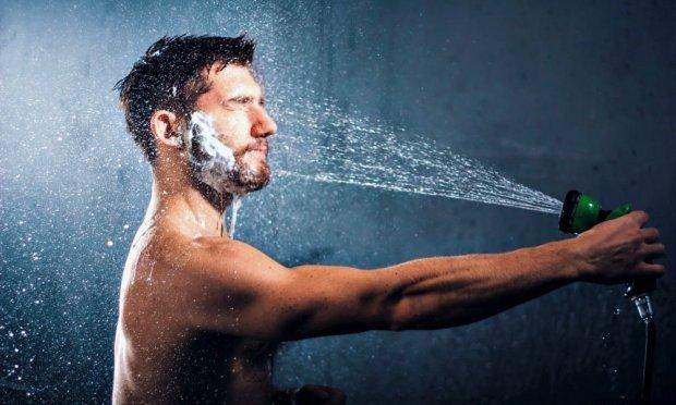 Uomo con la barba si lava usando una pompa da giardino